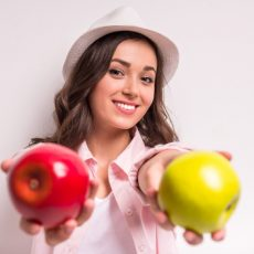 young-smiling-woman-is-holding-red-green-apple_85574-11032